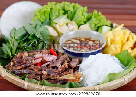 Pork dipping fish sauce served with rice vermicelli, paper rice and vegetables, typical Vietnamese cuisine so called THIT NGAM NUOC MAM. - stock photo