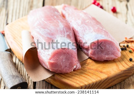 Pork fillet. Raw meat with  spices on cutting board - stock photo
