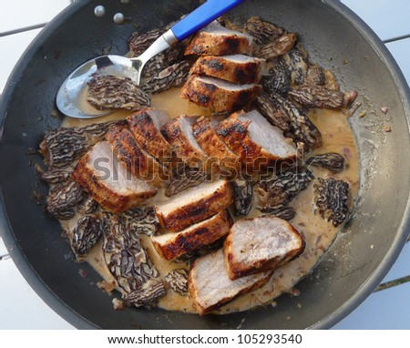 Pork Fillet with morels in frying pan during camping - stock photo