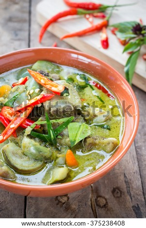 pork  green curry with coconut milk, pork and spices in a dish and put on an old wooden table.