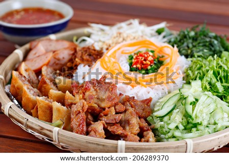 Pork grilled spring rolls and fresh sausages with rice noodle and vegetable, Vietnamese typical cuisine so called BUN THIT NUONG. - stock photo