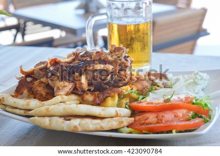 Pork gyros on a plate with salad and a glass of bear - stock photo
