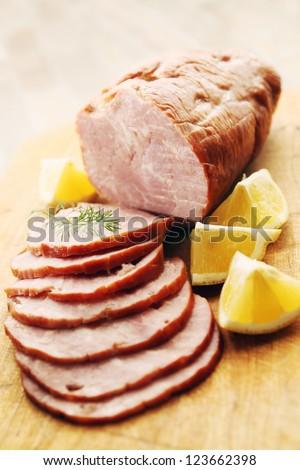 pork ham sliced �¢??�¢??lemon on a wooden board - stock photo