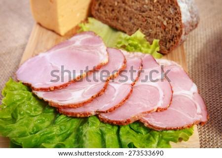 Pork ham slices with lettuce, rye bread and cheese on wooden background - stock photo