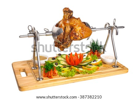 Pork knuckle on a spit on a cutting board with fresh vegetables and mustard in saucers. Isolated on white - stock photo