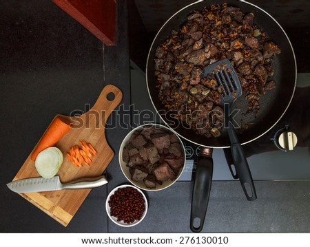 Pork liver stewed with onions and carrot and red beans in  frying pan view 2 - stock photo