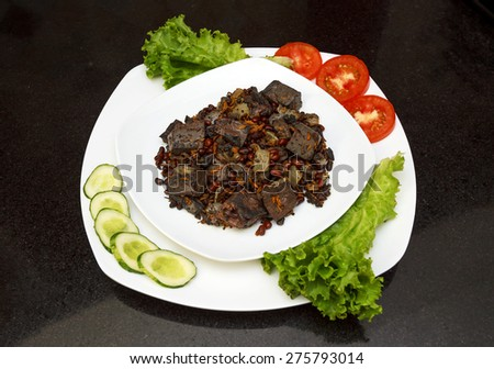 Pork liver stewed with onions and carrots and red beans served with fresh vegetables on white plate view 1 - stock photo