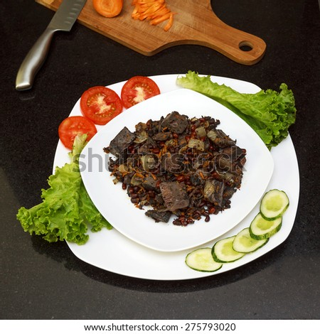 Pork liver stewed with onions and carrots and red beans served with fresh vegetables on white plate view 3 - stock photo