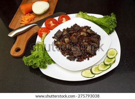 Pork liver stewed with onions and carrots and red beans served with fresh vegetables on white plate view 2 - stock photo