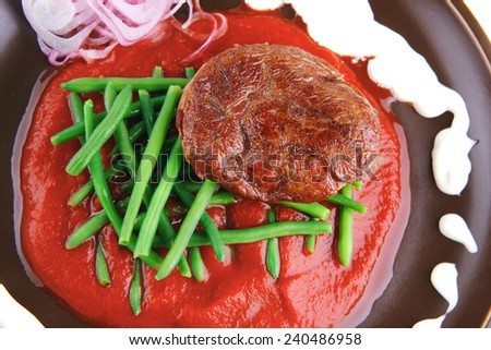 pork medallion served on tomato sauce with green peas on dark plate isolated on white background - stock photo