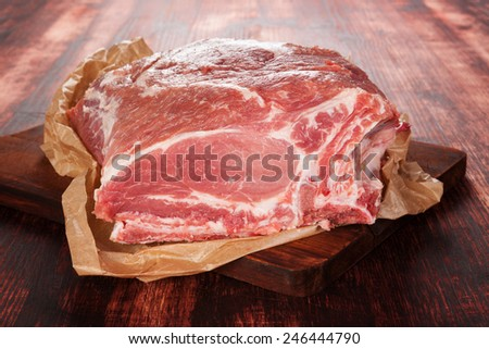 Pork neck piece on baking paper on brown wooden chopping board on brown wooden background. Culinary meat eating.