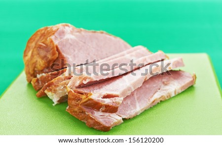 Pork neck rests on green cutting board. - stock photo