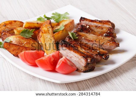 Pork ribs, potatoes and tomatoes on a plate close-up on the table. horizontal - stock photo