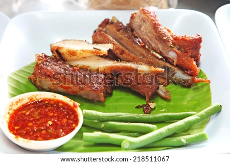 Pork ribs served with chilli sauce and peas