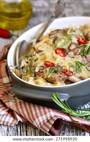Pork ribs stewed with sour cabbage on a wooden table. - stock photo