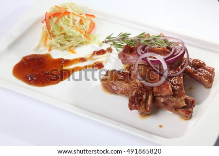 pork ribs with sauce and rosemary on plate