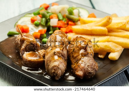 Pork rolls with french fries and vegetable - stock photo