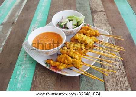 Pork satay sauce and side salad on a plate. Vintage wooden table - stock photo