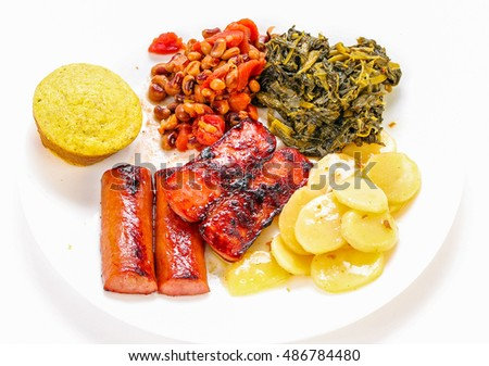 Pork sausage links on white plate with turnip greens; hoppin' John Peas; potatoes and cornbread muffin.  Strong back light on white background with copy space.