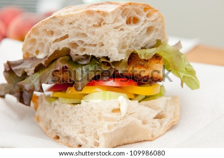 pork schnitzel sandwich on fresh baked bread with heirloom tomatoes and lettuce - stock photo