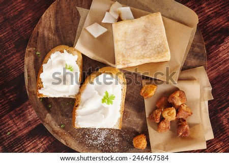 Pork scratchings, bacon and bread with lard spread on wooden kitchen board on wooden background, top view. Traditional british eating.  - stock photo