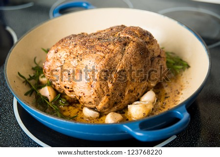 Pork Shoulder Roasting in Oven with Herbs and Lemons - stock photo