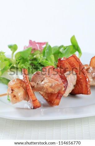 Pork skewer with mixed salad greens