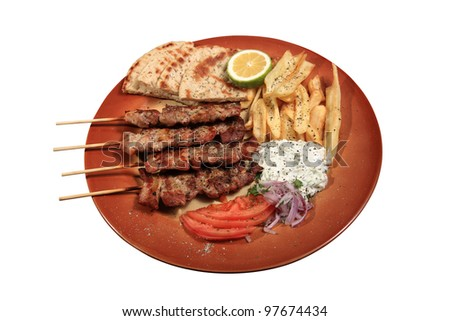 pork skewers served on a plate with fries tzatziki pita and tomato in a greek style