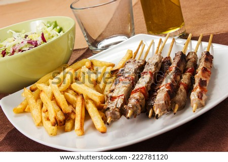 Pork skewers with french fries on the table