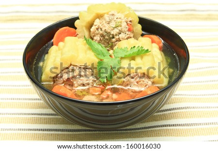 Pork soup with bitter gourd and carrot in black bowl. - stock photo