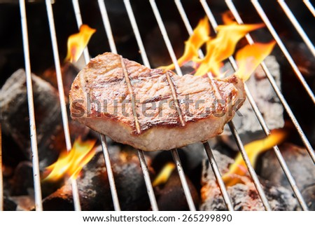 pork steak cooking over flaming grill - stock photo