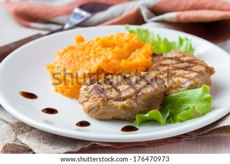Pork steak fried on a grill with mashed sweet potatoes, delicious homemade dish