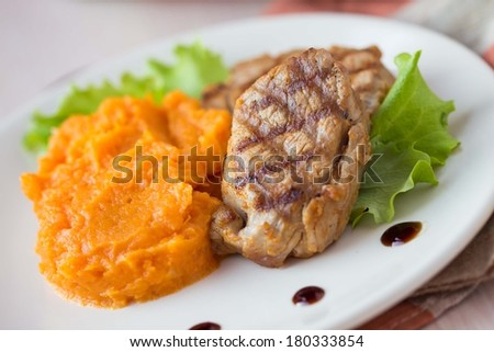 Pork steak fried on a grill with mashed sweet potatoes, delicious homemade dish - stock photo
