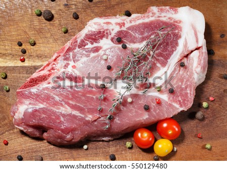 Pork steak on the wooden background with pepper, thyme and cherry tomatoes