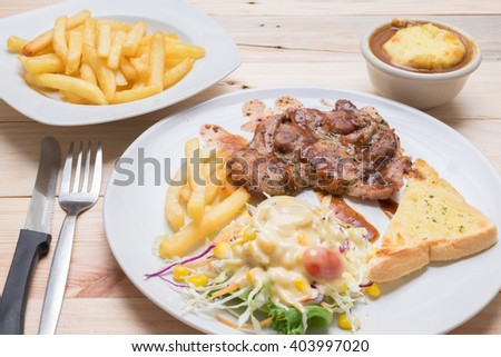 pork steak with bead ,french fries, Mashed potato, salad on dish top view on wooden background - stock photo