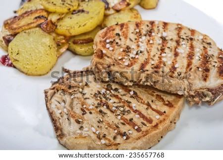Pork steak with salt pepper and cumin with fried potatoes on white plate - stock photo