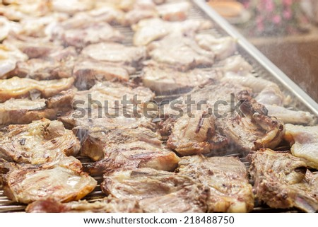 Pork steaks and chicken meat grilling on a barbecue. Retro colors - stock photo