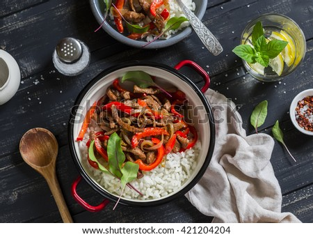 Pork stir fry with red peppers and rice in a pot, homemade lemonade with lemon on a dark wooden background. Delicious healthy lunch. Top view - stock photo