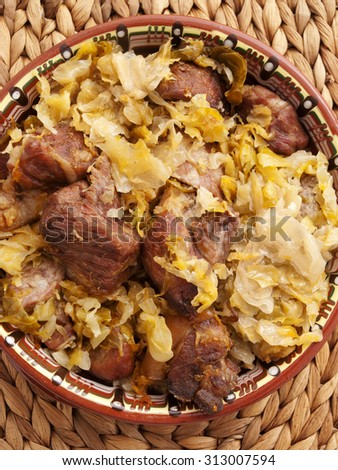 Pork with cabbage stew. Shot from above over wooden background. - stock photo