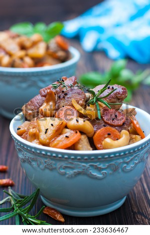 pork with carrots, pineapple, cashew nuts and chilli in a blue bowl on a wooden table. Asian cuisine