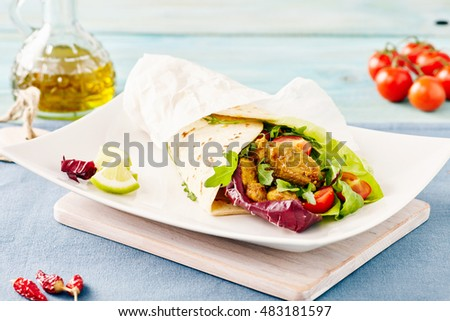 pork wraps on a white serving plate with rocket and lettuce, pastel colors