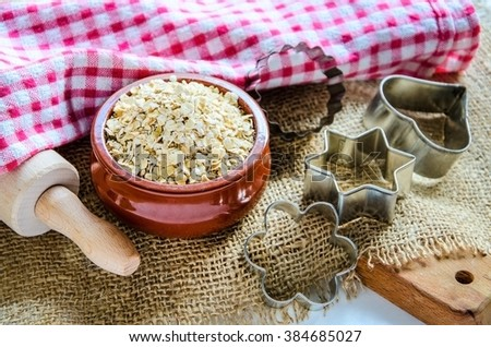 Porridge oats in ceramic bowl with   rolling pin and baking molds