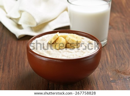 Porridge oats with banana slices and glass of milk on wooden table - stock photo