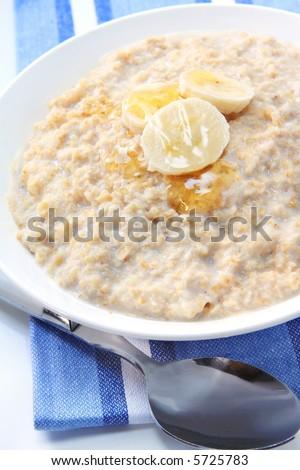 Porridge with banana and honey.  Healthy oatmeal breakfast. - stock photo
