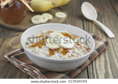 Porridge with bananas and syrup in a  bowl on the table