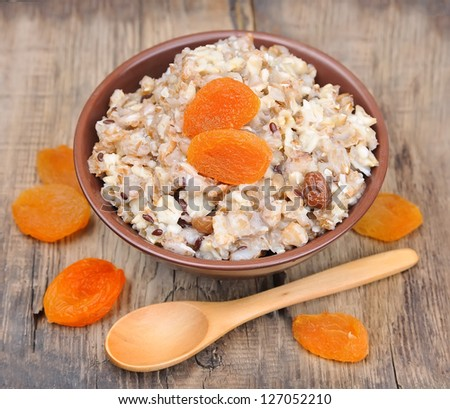 Porridge with dried apricots on wooden background. Home cuisine.Lunch - stock photo