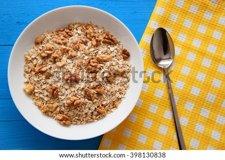 Porridge with nuts. Oatmeal with  with walnuts. Oatmeal in a bowl. Spoon, a plate of porridge. Diet menu. Weight loss, weight loss, diet concept.. Top view point. - stock photo
