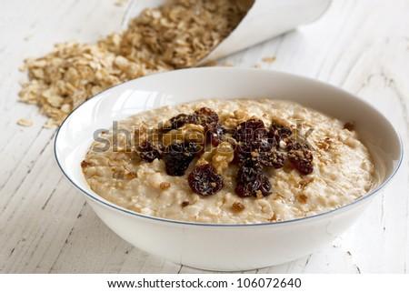 Porridge with walnuts, raisins and brown sugar.  Delicious oatmeal. - stock photo