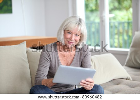 Porrtait of senior woman using electronic tablet at home - stock photo