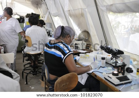 PORT-AU-PRINCE - AUGUST 26:  An Haitian pathologist testing blood samples of patients in a temporary pathological tent on August 26 2010 in Port-Au-Prince, Haiti. - stock photo